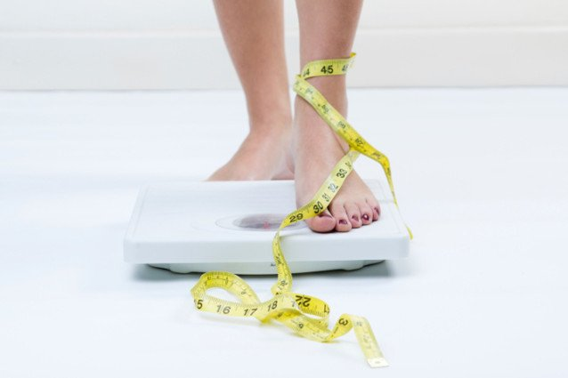 standing on scale with tape measure
